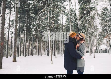 Coppia romantica baciare mentre permanente sulla coperta di neve campo nella foresta Foto Stock