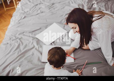 Angolo di alta vista di felice la madre e il bambino con forniture scolastiche su letto di casa Foto Stock