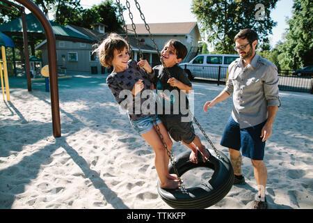 Padre guardando i bambini che giocano su tire swing in cortile Foto Stock