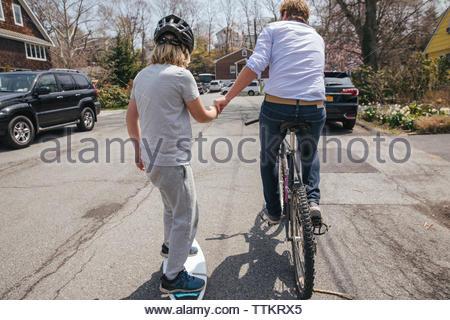 Vista posteriore del padre bicicletta equitazione mentre assistono figlio di skateboard su strada Foto Stock