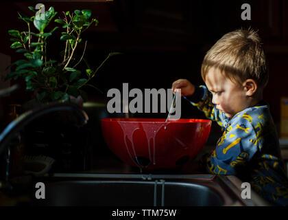 Ragazzo giocando con il cibo in cucina Foto Stock