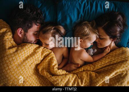 Famiglia di quattro persone dormono insieme nel letto tenendo i bambini Foto Stock