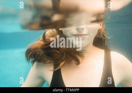 Sezione mediana della ragazza di nuoto sott'acqua nel lago Foto Stock