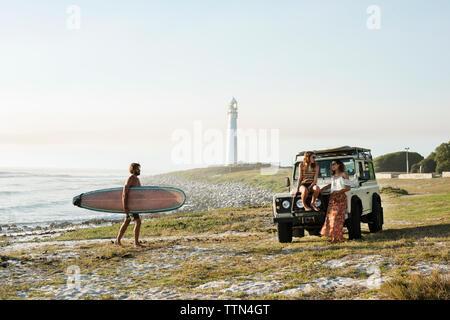 Uomo con la tavola da surf a piedi verso amici di sesso femminile presso la spiaggia contro il cielo chiaro Foto Stock