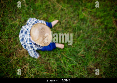 Vista aerea del bambino seduto sul campo di erba in posizione di parcheggio Foto Stock