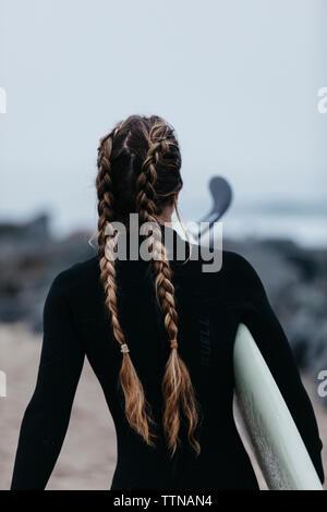 Vista posteriore della donna con treccia di capelli lunghi che trasportano le tavole da surf mentre passeggiate in spiaggia contro sky Foto Stock