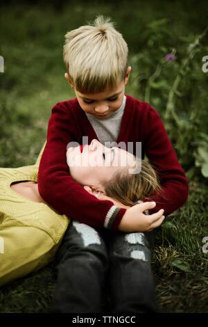 Figlio abbracciando la madre sul campo in campagna Foto Stock