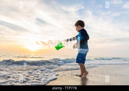 Bambino benna basculante in spiaggia mentre si tiene un dollaro di sabbia Foto Stock