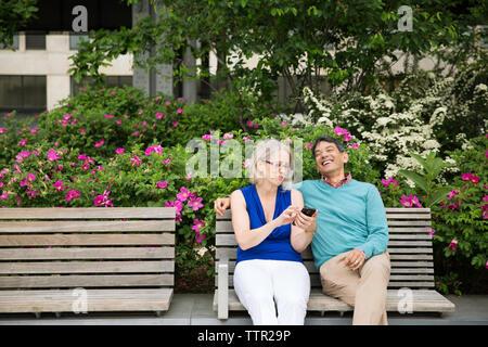 Felice Coppia matura utilizzando smart phone seduta sul banco in posizione di parcheggio Foto Stock