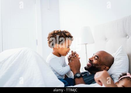 Padre Felice giocando con il figlio mentre vi rilassate sul letto contro la parete a casa