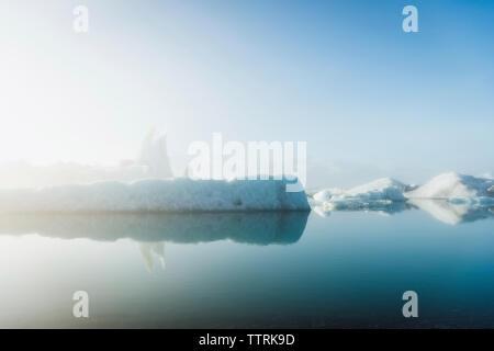 Visione idilliaca di iceberg in mare contro il cielo durante la nebbia meteo Foto Stock