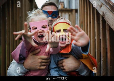 Ritratto di bambini con padre in costumi di supereroi Foto Stock
