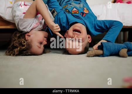 Ragazzo e ragazza fratelli ridere insieme in posizione capovolta sul letto Foto Stock