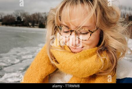 Ritratto di donna bionda con gli occhiali a sorridere mentre in spiaggia