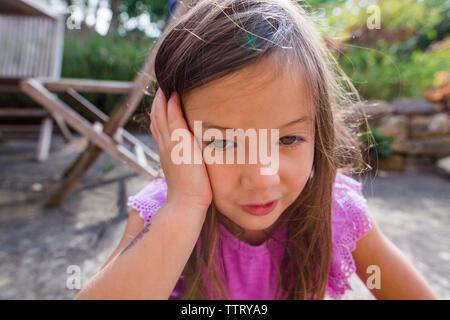 Close-up di pensosa ragazza carina appoggiato la testa sulla mano mentre seduto in cantiere