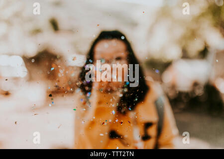 La donna la spruzzatura di coriandoli su strada Foto Stock
