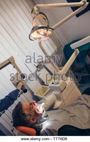 Ritagliate la mano del dentista utilizzando apparecchiature dentali mentre esaminando denti del paziente Foto Stock