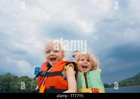 Basso angolo vista delle sorelle in canoa con padre in background contro nuvole temporalesche Foto Stock