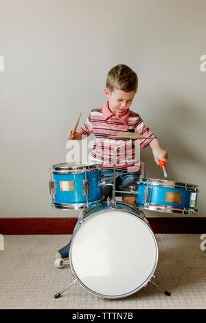 Carino boy suonando la batteria mentre è seduto contro la parete a casa Foto Stock