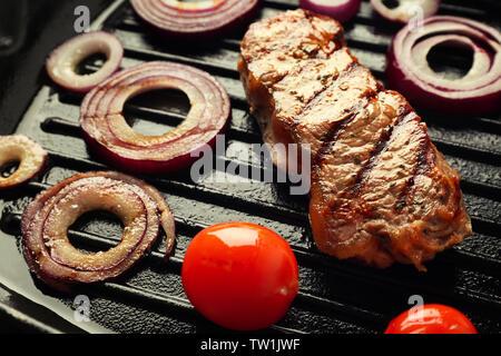 Preparazione della bistecca con anelli di cipolla e pomodori in padella per grigliare, primo piano Foto Stock