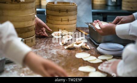 Team taiwanesi di chef cucinare cibi tradizionali. Chef asiatico rendendo gnocchi di fresco nel ristorante di Taiwan. Gli uomini mani cook e pasta prepairing