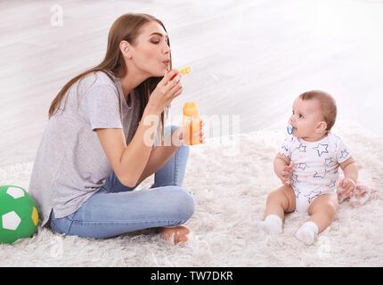 Giovane madre e simpatici baby giocando sul pavimento a casa Foto Stock