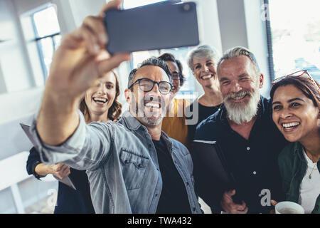 Il successo del team aziendale tenendo selfie insieme. Gruppo multirazziale delle persone che prendono selfie presso l'ufficio. Foto Stock