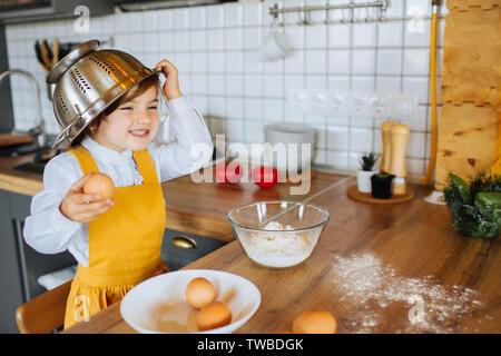 Un po' di sorridente ragazza aiutando la madre per cuocere i biscotti in forno in cucina. Azienda scolapasta sopra la sua testa a ridere. Foto Stock