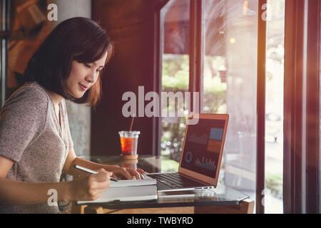Isolato mockup immagine di laptop e la giovane donna di affari in abbigliamento casual seduta a tavola in cafe e la scrittura nel notebook. Il freelance che lavorano in caffè Foto Stock