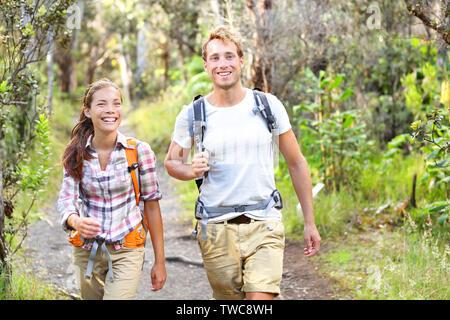 Attività outdoor escursionismo coppia felice - gli escursionisti a piedi nella foresta. Escursionista giovane ridendo e sorridendo. Gruppo multirazziale, uomo caucasico e donna asiatica sulla Big Island, Hawaii, Stati Uniti d'America. Foto Stock
