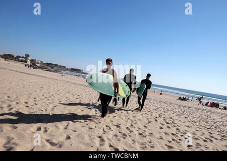 Giovani uomini che trasportano le tavole da surf in sole primaverile di camminare sulla spiaggia di sabbia a Matosinhos Porto Portogallo Europa KATHY DEWITT Foto Stock