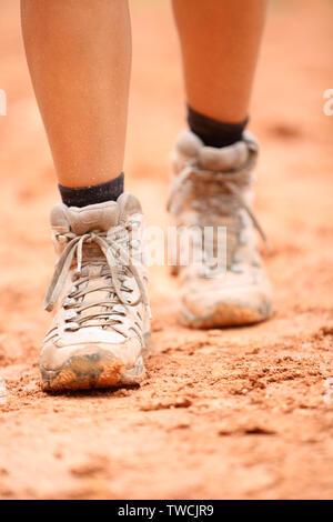 Scarpe da trekking - close up di sporco escursionista scarpe. Piedi di donna femmina e gli escursionisti calzature calzatura camminando sul sentiero sterrato escursione il percorso outdoor in natura. Foto Stock