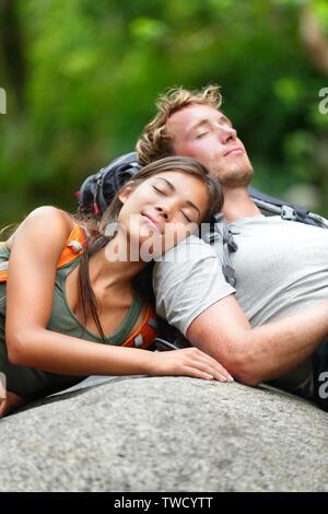 Escursionismo coppia amanti del sonno rilassante in natura. Ha cercato di appoggio per gli escursionisti sdraiati all'aperto prendendo una pausa da escursione. Giovane donna asiatica e uomo caucasico. Foto Stock