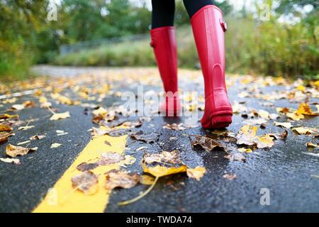 Autumn Fall concetto con foglie colorate e stivali di gomma all'esterno. Close up di donna piedi in stivali rossi. Foto Stock