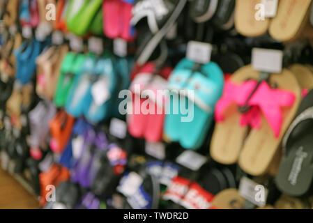 Immagine sfocata della fila di sandalo colorati appesi in negozio Foto Stock