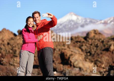 Giovane tenendo selfie escursioni nella splendida natura con smart phone. Coppia felice passeggiate godendo di vista e scattare foto con lo smartphone. L uomo e la donna dal vulcano Teide Tenerife, Isole Canarie. Foto Stock