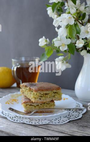 Torta con cavolo ripieno su una piastra su un di legno tabella grigia con un vaso di fiori con una tazza di tè e limone.prodotti da forno Foto Stock