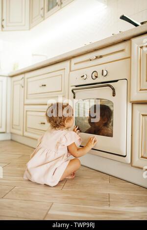 Femmina bambino seduto sul pavimento in corrispondenza del forno di cottura Foto Stock