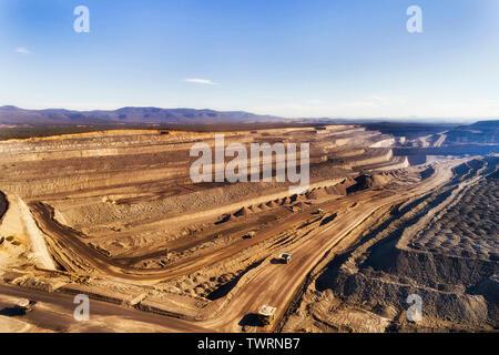 Deep exhavation di combustibili fossili minerali da taglio aperto nero miniera di carbone nella Hunter Valley bacino di carbone di Australia con macchine industriali, camion e e Foto Stock