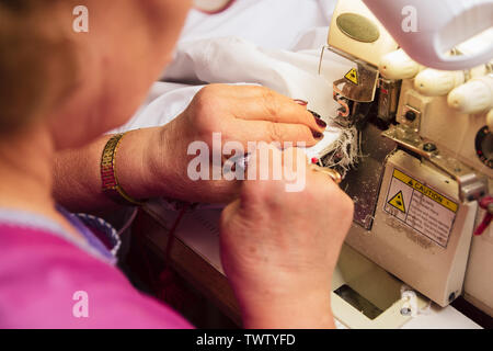 Una donna anziana cuce su una macchina da cucire sarto ricama in produzione. pensionato impegnato hobby preferito. Foto Stock