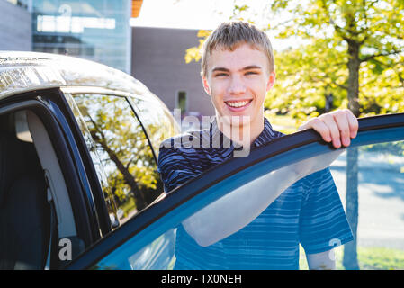 Adolescente di uscire della sua vettura il primo giorno di scuola. Foto Stock