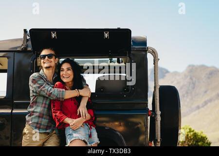 Matura in piedi accanto a loro auto in autostrada. Uomo che abbraccia la sua donna in piedi all'aperto e guardando lontano sorridente. Foto Stock