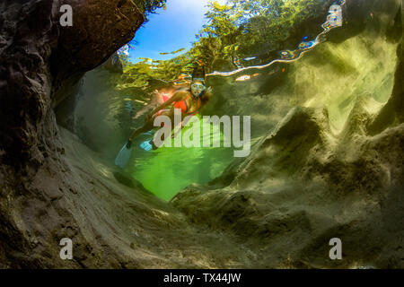Austria, Salzkammergut, giovane donna snorkeling nel fiume di montagna Weissenbach