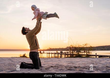 In Germania, in Baviera, Herrsching, padre e figlia giocando sulla spiaggia al tramonto Foto Stock