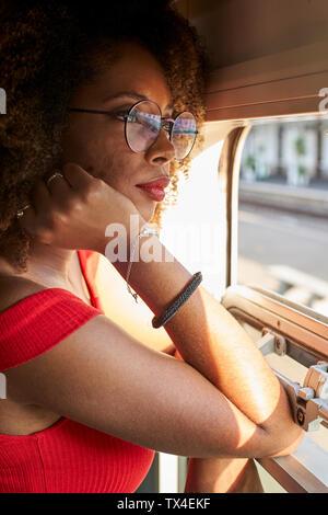 Giovane donna su un treno guardando fuori della finestra Foto Stock