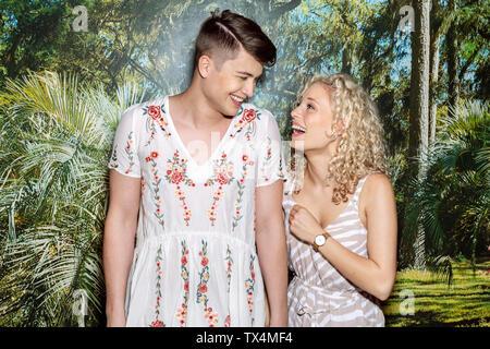 Coppia giovane in piedi di fronte a uno sfondo fotografico, uomo che indossa blusa con motivo floreale