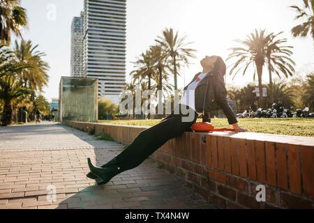 Giovane donna seduta su una parete, godendo di luce solare Foto Stock