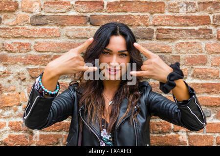 Ritratto di giovane donna vestita di nero giacca di pelle e mostra rock and roll segno, muro di mattoni Foto Stock