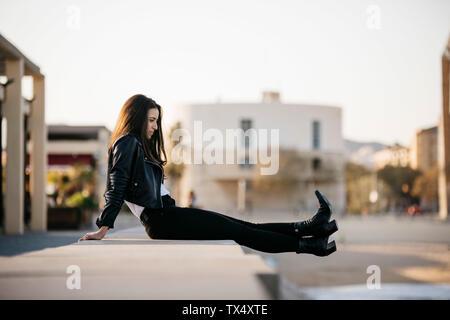 Giovane donna seduta su una parete Foto Stock