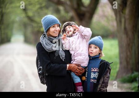Ritratto di felice madre con figlio e figlia piccola in un parco Foto Stock